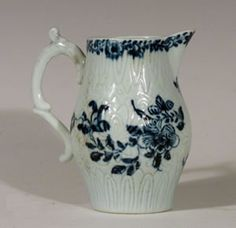 A Liverpool porcelain milk jug of a rare barrel shape. It was made at the Richard Chaffers factory. The handle form was subsequently used at the Philip Christian and Seth Pennington factories. The body is lightly moulded with a chrysanthemum pattern and painted in underglaze blue.    c.1760-65
