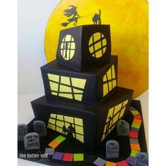 """Look closely....this is one naughty haunted house! In honor of my client's """"Draw What?"""" Game which is like adult pictionary  I created a funky haunted house cake with asymmetrical tiers frisky sihouettes and ripped-from-the game tombstones! The path around the house is like the game board. New for us....the huge painted moon backdrop....love how it finished the piece with the sexy witch! #pumpkincake #chocolatechocolatechipcake #cocopassioncake #drawwhat? #hereliesdirtysanchez #doggiestyle…"""