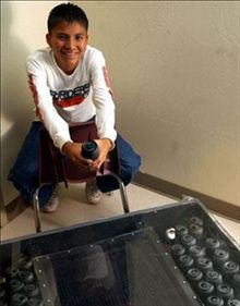 """Garret Yazzie, 7th-grader who made a solar-powered water heater from 26 aluminum cans and a '67 Pontiac radiator. His heater could heat water for bathing and raise the indoor air temperature by 45 degrees Fahrenheit. He was inspired to help his little sister, who suffered asthma from the fumes of their coal burning stove. Now known as """"the junk-yard genius,"""" Garrett's efforts attracted the attention of Extreme Makeover, resulting in a new green home for his family."""