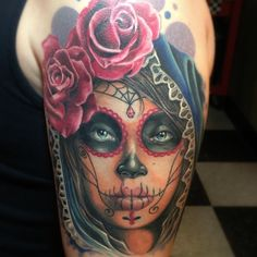 Day of the dead Tattoo with woman looking straight into eyes with rose symbols
