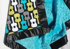 Minky and Satin Baby Blanket- Michael Miller Lagoon Groovy Guitars with Teal Blue Minky and a Black Satin Trim - Personalization Available. $48.00, via Etsy.