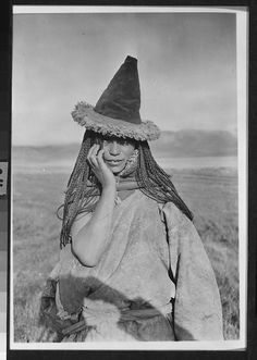 """Shakurj Tibetan nomad woman with a sheepskin hat and 108 braids in her hair in the grasslands near Koko Nor dated Sept. 28, 1925: """"...their hair was braided into tiny queues said to be 108 in honor of the 108 vol. of the Tibetan classic the Kandjar. Her face was ruddy and on her head she wore a cornu-copia hat of sheepskin."""" Ko-ko Nor Lake, Ch'ing-hai. Camp, Tibet. Joseph Rock - On Shadow"""