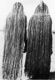 Africa | Two women with hairstyles made of braided sinew (eefipa). Mbalantu, Wambo group, Namibia, 1940s. | Photo: M. Schettler. From Scherz et al. 1992:39. ||  To create this hairdo, plaited extensions from previous coiffures were removed and additional plaits attached to lengthen them until they hung to the ankles. This style is worn by young women who take part in the ohango initiation ceremony.