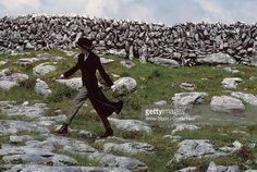 Model Nadja Auermann walking across the boulder-strewn scenery of Burren…