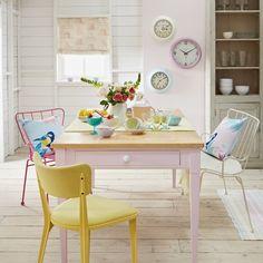 Retro Pastell Esszimmer. Eine einfache Trio Retro-Uhren macht eine ins Auge fallende Funktion in diesem Esszimmer. Eine bemalte Holztisch mit Metallsitzgelegenheiten für eine leben-im Blick zusammengefasst.                                                                                                                                                                                 Mehr