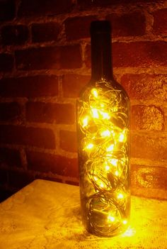 so awesome - recycled wine bottle lanterns using christmas lights! http://www.bobvila.com/blogs/wine-bottle-lanterns/#