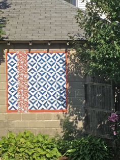 Decorative geometric mural painted on the outside wall of a concrete garage.
