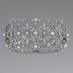 OOCH, EARLY 20TH CENTURY Of hinged plaque design, centring on a frieze of Fleur-de-Lys motifs, to a trellis background and stylised scroll border, accented with circular- and rose-cut diamonds, detachable brooch fitting.