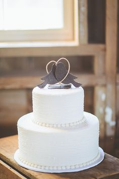 A two-tier white wedding cake with a lovebird topper | Brides.com