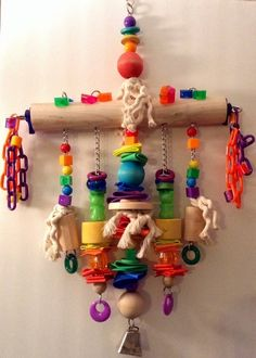 """This toy is 4lbs of fun for the XL birds. It's 28"""" long. It's Birch base is a 14"""" long and 2"""" thick. It's strung with Heavy Nickel Plated chain. Lots of Marbella rings, acrylics , plastic chain, Foam and a Large Cow Bell. The sides have 2"""" Tri Beads that spin. It also has heavy eye hooks on each side to attach chain to hang as a perch. Nice heavy pieces of wood for your flocks chewing enjoyment. This is great for Macaws & Cockatoo's #Macaw #Parrot #BirdToy #COCKATOO #Makeyourownbirdtoys"""