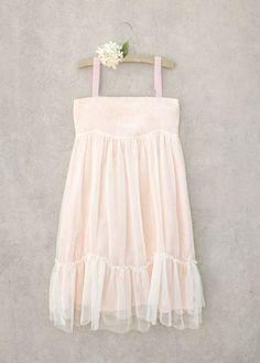 This pretty pale pink dress has a unique tulle overlay design and a gathered ruffle at the hem. Classy, sweet, and perfect for any fashionista with an affinity