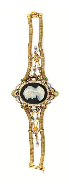 GOLD, HARDSTONE CAMEO, COLORED STONE, ENAMEL AND SEED PEARL BRACELET.  Centered by an oval-shaped sardonyx cameo featuring the bust of a maiden, framed within black and white enamel with black and blue flourishes, further enhanced by 12 cushion-cut rubies, four emerald-cut emeralds and seven seed pearls, length 7¼ inches, mid-19th Century.