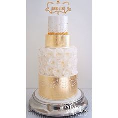 {Gold Elegance} This wedding cake was all about class and gold. Textured gold foil and delicate wafer flowers make for a elegant combination.