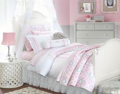 An ultra-feminine color palette of pink and white is offset with a few gray accents in this bedroom for a young girl.