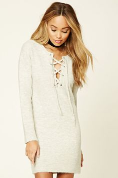 A sweater knit dress featuring a round neckline that opens into a lace-up front with grommets, long sleeves, and an oversized silhouette.