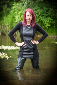 Redhead in black multimedia leather dress and thigh waders in the water