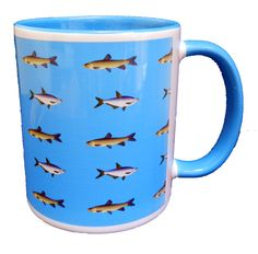 Lots of lots of fish swimming in the sea on this Ceramic Mug. With an attractive blue handle and inner. A good quality ceramic mug which is dishwasher proof. Height is 9.5cm, diameter 8.2cm, with a capacity of 310 ml. From the Series 6 Animals Range by Half a Donkey Ltd. www.halfadonkey.co.uk