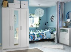 A light small bedroom furnished with a white metal bed for two combined with a bedside table, chest of drawers and a wardrobe with a mirror door.