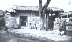 A rice shop in Seoul. Note Yangban woman with coat-veil on right. Percival Lowell photo ca. 1882.
