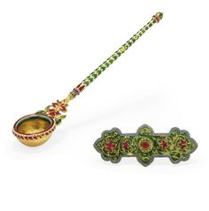 AN ENAMELLED GOLD SPOON AND AN ENAMELLED GOLD PANEL  INDIA, 19TH CENTURY. The handle with tapering finial, an openwork floral motif joining the handle to the bowl, the rim enamelled in red and white, the handle with alternatively white and green bands of chevrons, small dent, the enamelled panel with floral arabesques, in good condition Spoon 4¾in. (12cm.) long; panel 2¼in. (5.6cm.) long