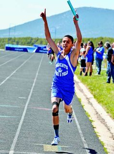 Questa's Juan Gomez raises his hands in celebration as he crosses the finish line first in the 4x400-meter relay, qualifying the relay team for state and helping QHS win the team title. Photo courtesy John Denne