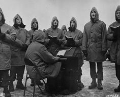 Christmas during WW2: US Army soldiers, stationed in Iceland, take the opportunity to sing the carols on Christmas Day 1942. They are all wearing their extreme weather kit, complete with thermal rubber boots. The trivia question would surely be where did they find the mini organ.