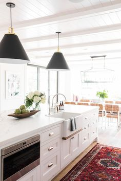 Beautiful white kitchen with black light fixtures over island and vintage rug