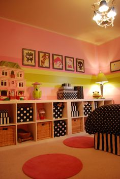 I like the storage in this playroom - a long row of two-tall cubbies with stuff displayed on top.  The polka dots are cute, too.  Cute kids room for a girl