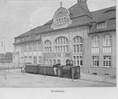 Schwarz-Weiß-Foto: großes Gebäude mit Lokomotive im Vordergrund