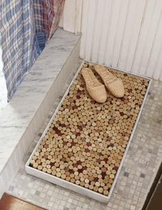 Wine cork bath mat. one modification. Instead of using a shadow box, which I feel will deteriorate over time (depending on the box you chose), I will build my own box constructed of cedar. Other ideas...make a larger size for kitchen....or use cut branches instead of wine corks for outdoor mat.