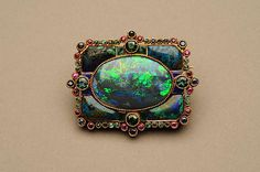 Gold, black opal, shattuckite, green tourmalines, emeralds, sapphires, rubies, and enamel. Marie Zimmermann