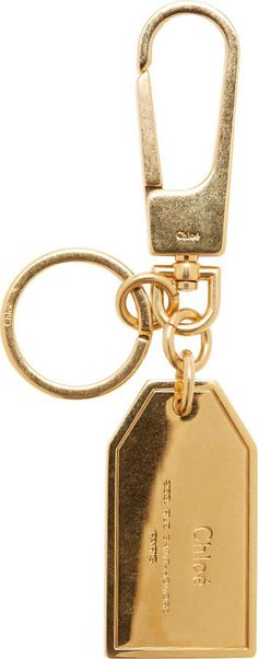 """Pendant key ring in gold-tone brass. Lobster claw clasp. Luggage-tag style pendant with tonal logo stamp. Approx. 4.5"""" length."""