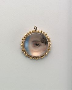 "Miniature of an Eye, Emily Drayton Taylor ~ ca. 1930 ~ 3/4"" diameter  Artist:  After Edward Greene Malbone              (1777-1807)  Watercolor on ivory in gold locket with beaded bezel."