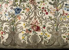Detail of material of Mantua, 1740-45. Embroidered silk with colored silk and silver thread. Leafy scrolls, latticed arcades & tassels are also featured, as well a profusion of realistically rendered flowers, including jasmine, morning glory, honeysuckle, peonies, roses, poppies, anemones, auriculas, hyacinths, carnations, cornflowers, tulips & daffodils. The flowers are worked in a variety of coloured silks in satin stitch & french knots. Silver thread delineates leaves & non-floral…