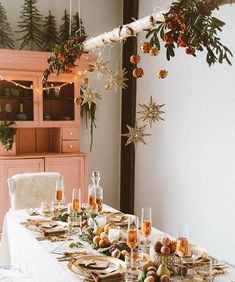 Christmas deco: hanging branch above table with oranges