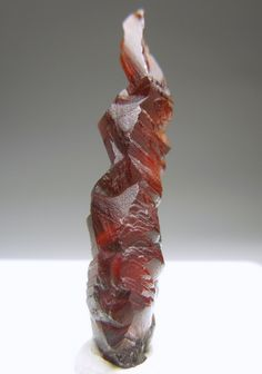 A beautiful crystal of orange-red Spessartine with a twisty sculptural shape.