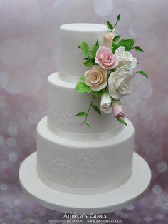 Bruidstaart met kanten bewerking  en suikerwerk boeket van rozen in perzik, roze en wit.