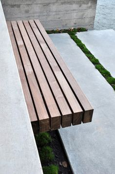 The bench is supported by custom steel brackets that are anchored to the concrete retaining wall. I've attached a detail for your reference. The design intent was to emphasize a floating plane of wood, rather than bringing attention to the connection.