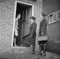 TRAINING QUEEN'S NURSES: DISTRICT NURSE TRAINING AT THE QUEEN'S INSTITUTE OF DISTRICT NURSING, GUILDFORD, SURREY, ENGLAND, UK, 1944 / A trainee District Nurse (right) accompanies a qualified District Nurse on a home visit. They are greeted at the door by the mother of a young girl recovering from pneumonia.