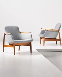 FINN JUHL, Pair of easy chairs, model no. NV53, circa 1953. Walnut, fabric, brass. Executed by cabinetmaker Niels Vodder, Denmark.