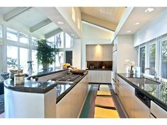 Contemporary kitchen with vaulted beam ceiling and tons of windows