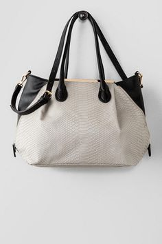 """The Serena Color Block Snakeskin Tote features a textured gray snakeskin middle accented by black faux zipper sides and golden bar edges. Finished with a zipper closure, inside pockets, & an optional shoulder strap.Carry this bagwhile wearing great tall boots and an edgy top.<br /> <br /> - 18"""" length x 11"""" height<br /> - 8"""" strap drop<br /> - 22"""" optional shoulder strap drop<br /> - Imported"""
