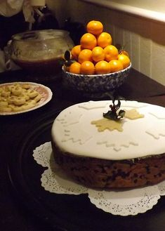 A traditional Twelfth Night cake (from an 1803 recipe), oranges, biscuits and a bowl of 'lambswool' punch decorate a Georgian-style dessert table at a recreation of a Twelfth Night party.