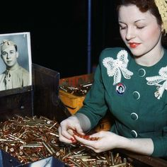 Fee Perez inspects .30 caliber bullets rifle and machine gun bullets at Remington Arms Company's Bridgeport, CT alongside a photo of her husband who was serving oversees during WWII.