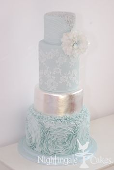- Pale blue wedding cake with silver accents, lace, ruffles, silver leaf and pleated top cake with fantasy ruffle flower