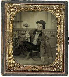 Occupation. Tintype portrait of a bearded gentleman,  holding a leather mallet in one hand an chisel in other, seated on an early daguerreotype camera. ca 1860s