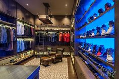 "Red Rock Contractors & Angelica Henry Design. Image of the entire ""his"" luxury walk-in-closet with extensive footwear storage, suit racks and brown leather armchair. [Decor Facelift]"