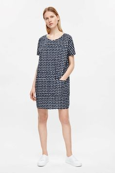 An oversized t-shirt fit with a low scoop back and tie detail, this dress is made from a patterned cotton poplin. Designed with relaxed proportions, it is completed with front in-seam pockets, short sleeves and neat finishes.