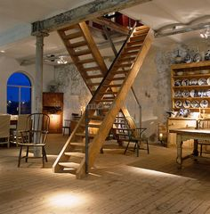A pair of ladder staircases leads from the open-plan living space to the upper floors of this converted warehouse
