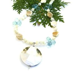The BEACH BEAUTY handmade necklace is perfect for a mermaid . . . or the loved one who wishes they were. Created with a balanced asymmetrical design, the summer necklace features a shimmering pendant created with two types of shells and a geometrical pattern.